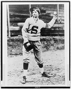 black and white photo of Mitchell, posing as if she's pitching