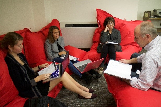 students and a professor sitting in bean bags