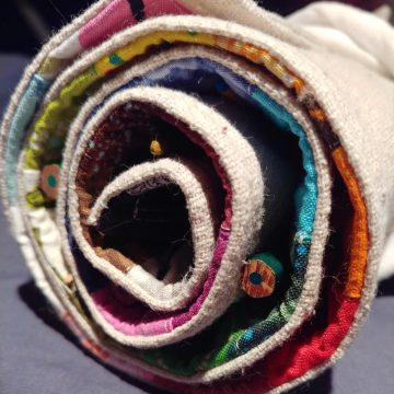 Fabric rolled into a spiral. Canvas on the outside, bright colors on the inside