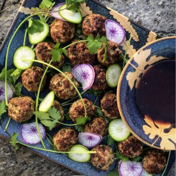 meatballs and star radishes with herb adornments and dipping sauce