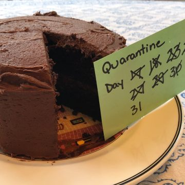 "Chocolate cake with card that says, ""Quarantine Day"" with some numbers crossed off leading to 31."