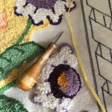rug hooking tool on partially completed flowers