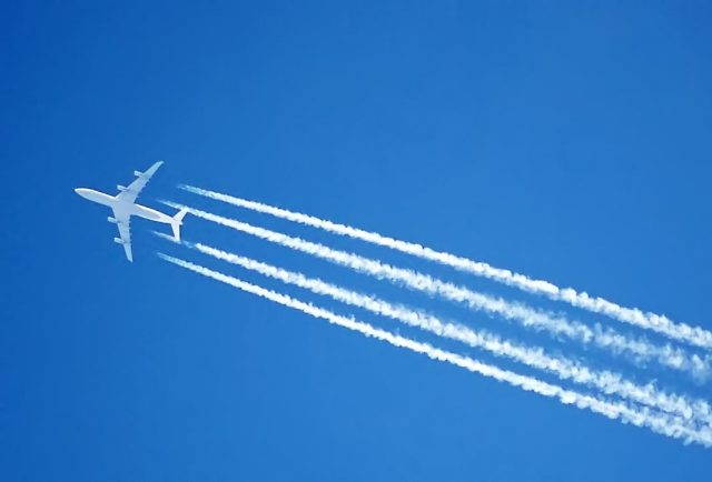 A jet plane in the sky with four contrails behind it.