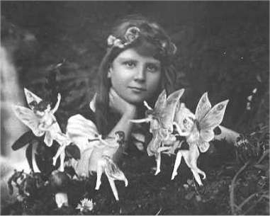 Frances Griffith with fairies dancing in front of her.