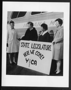 image of four women standing in front of a bus holding a sign that reads state legislature here we come YWCA