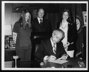 image of man signing a bill into law and two women and a man standing behind him