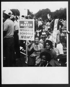 image of a group of demonstrators one holding a sign that says we march for integrated schools now