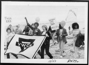 image of protesters marching on a beach holding signs for the ERA