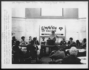 image of conference with women standing at podium in front of a banner that reads the elimination of racism