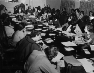 black and white photograph of women and girls sitting at a long table listening and taking notes