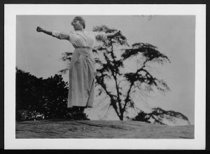 photograph of woman standing outside possibly on top of hill or mountain stretching arms wide