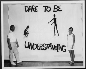 black and white photograph of a man and a woman standing in front of a banner that says dare to be understanding