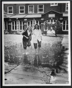 black and white photograph of two women with pants rolled up standing in a large puddle