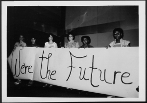 women holding a banner that reads we are the future