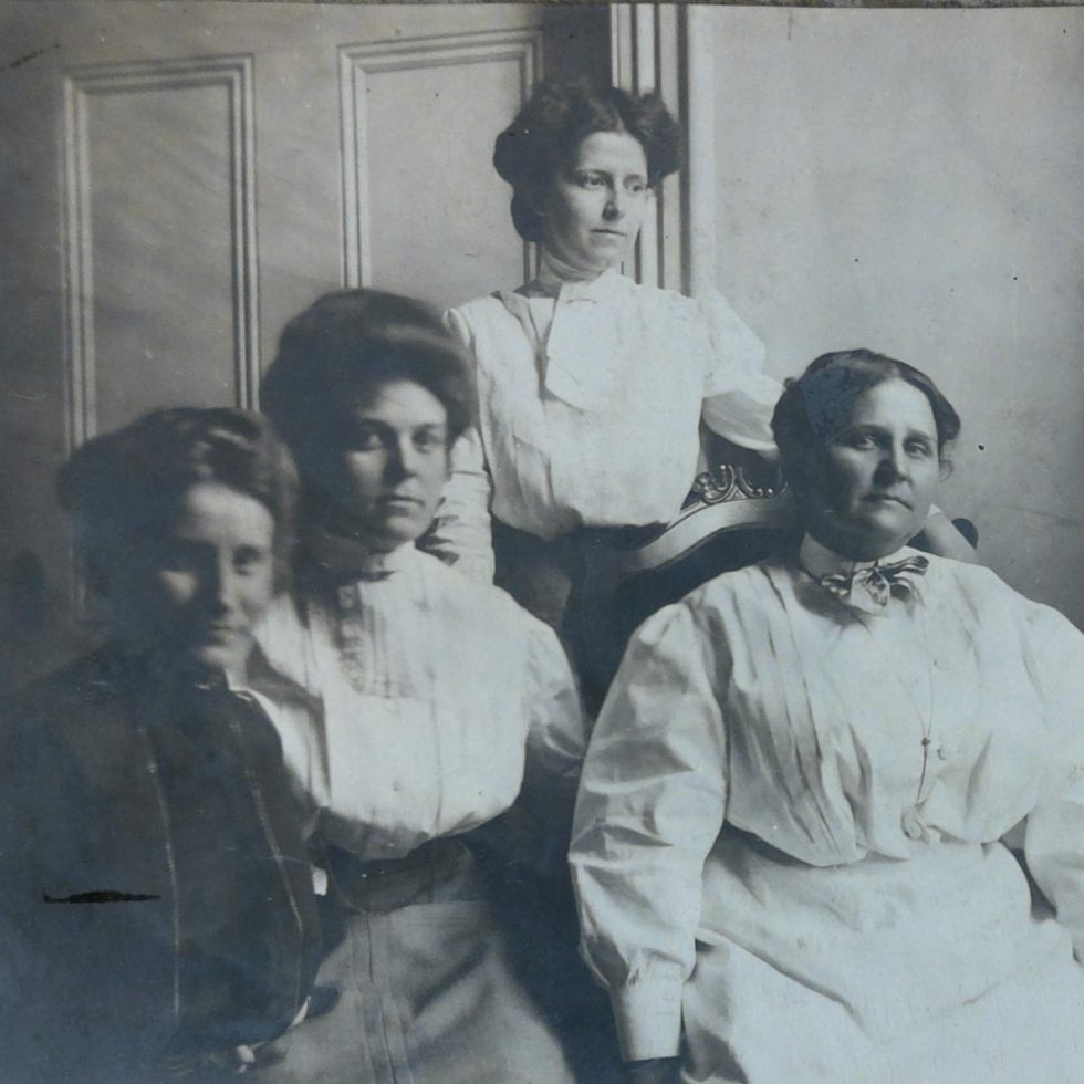Picture of three young white women sitting or standing next to an older white woman.