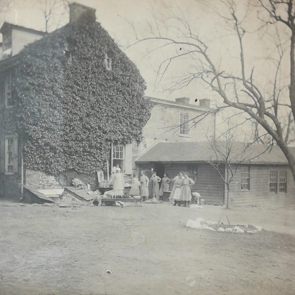 Image of a group of girls outside a house partially covered in ivy.