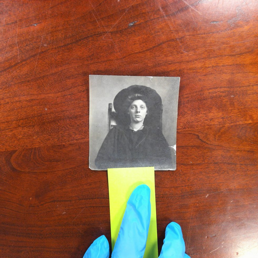 Picture of a white girl sitting and looking directly into the camera. A hand in a blue glove with a yellow piece of paper is touching the image.