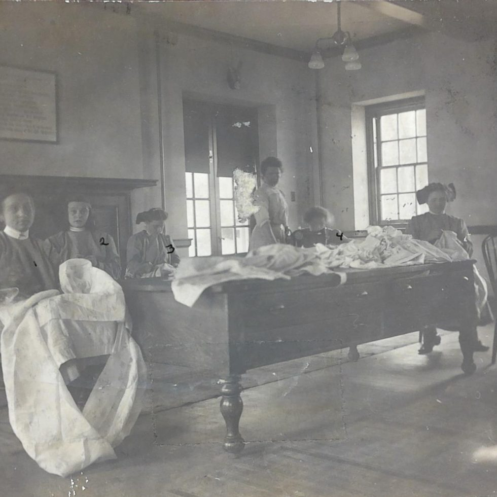 Images of girls sitting working with large pieces of whtie cloth.