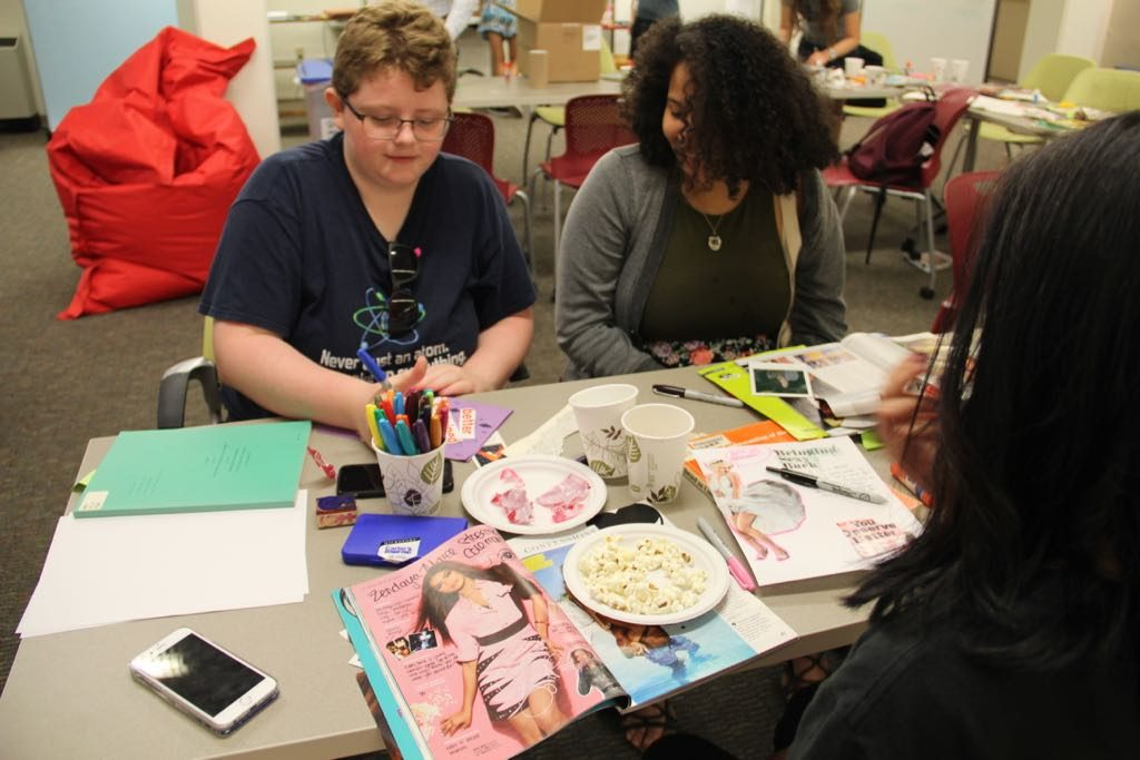 Two participants in the workshop making a zine page together