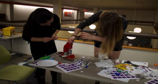 two students using a button maker