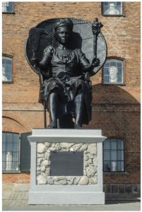 Photo by David Berg. Visual art by Jeannette Ehlers & La Vaughan Belle, I am Queen Mary. Sculpture of Black Queen Mary holding scepter on a throne in front of a brick building with images of white male saints in the windows.