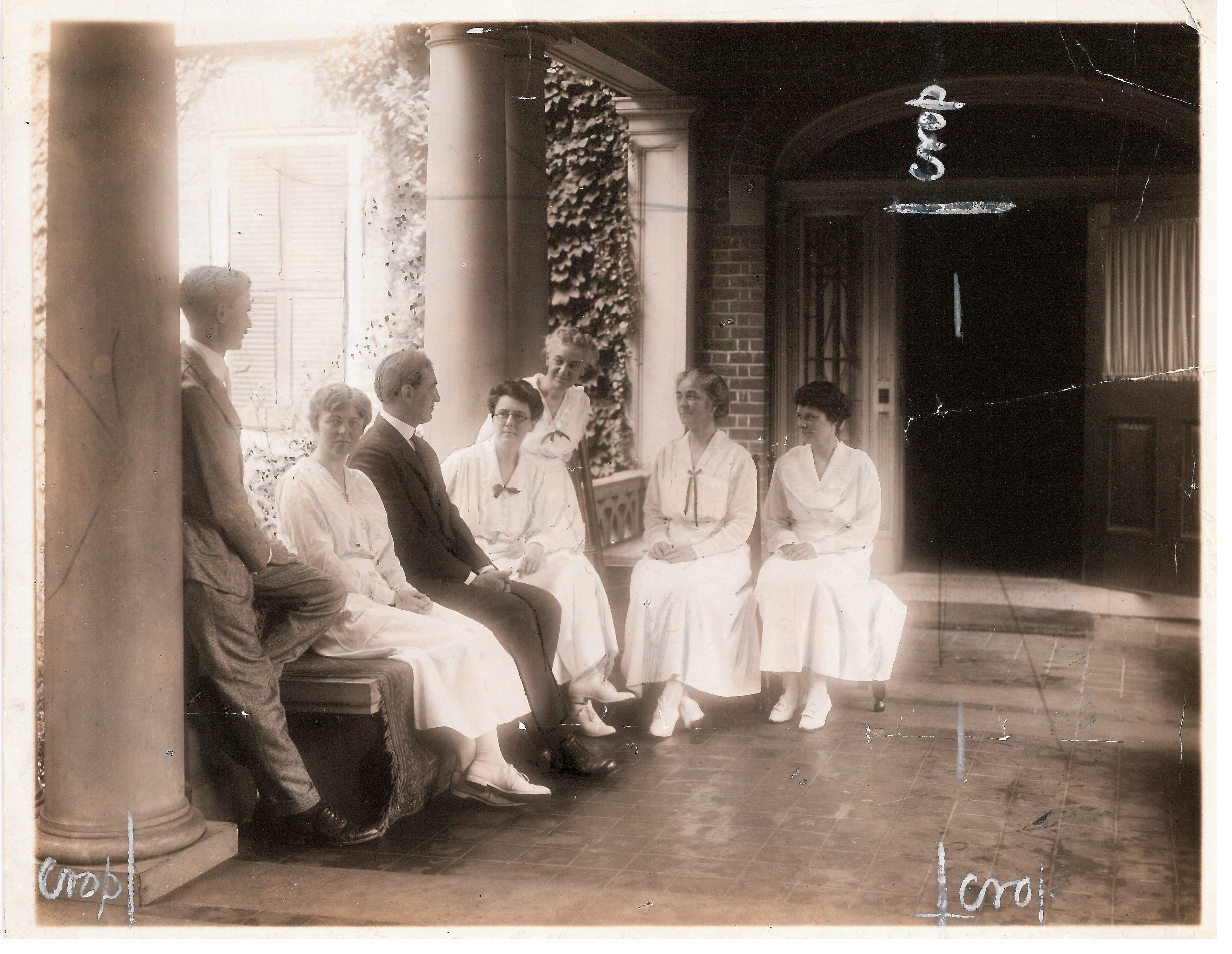 Black and white photo of faculty in formal dress on porch.