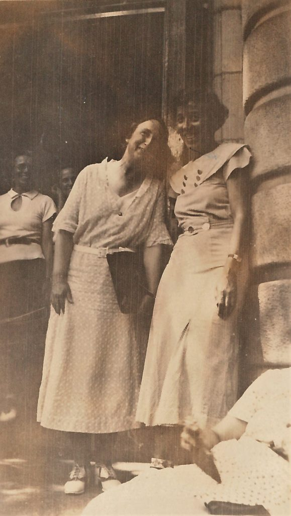 Black and white photo of Bertha Capen Reynolds leaning into Annette Garrett, both looking at camera.