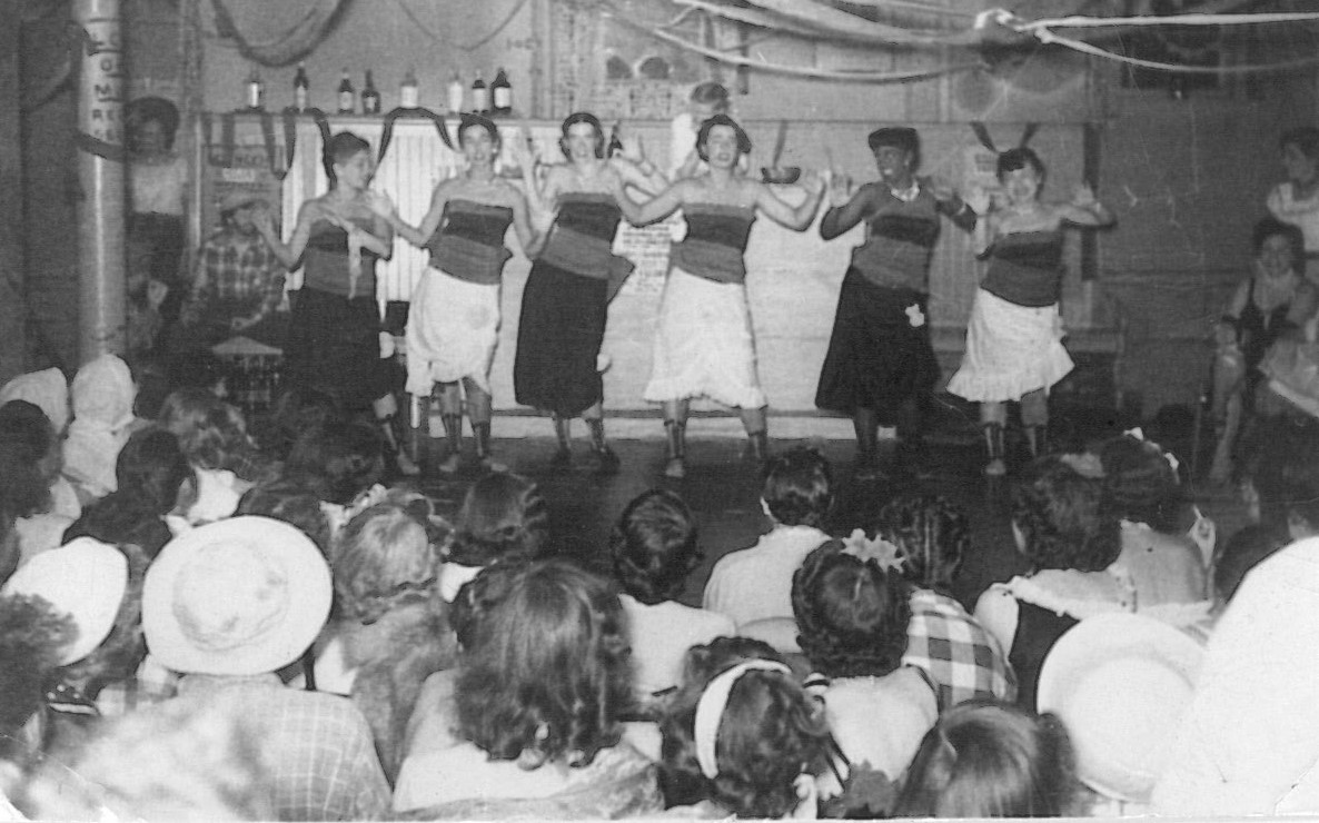 Black and white photo of six people on stage dancing in a line.