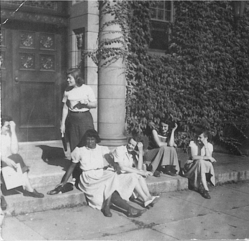 black and white photo of four people sitting in skirts and one person in pants standing.