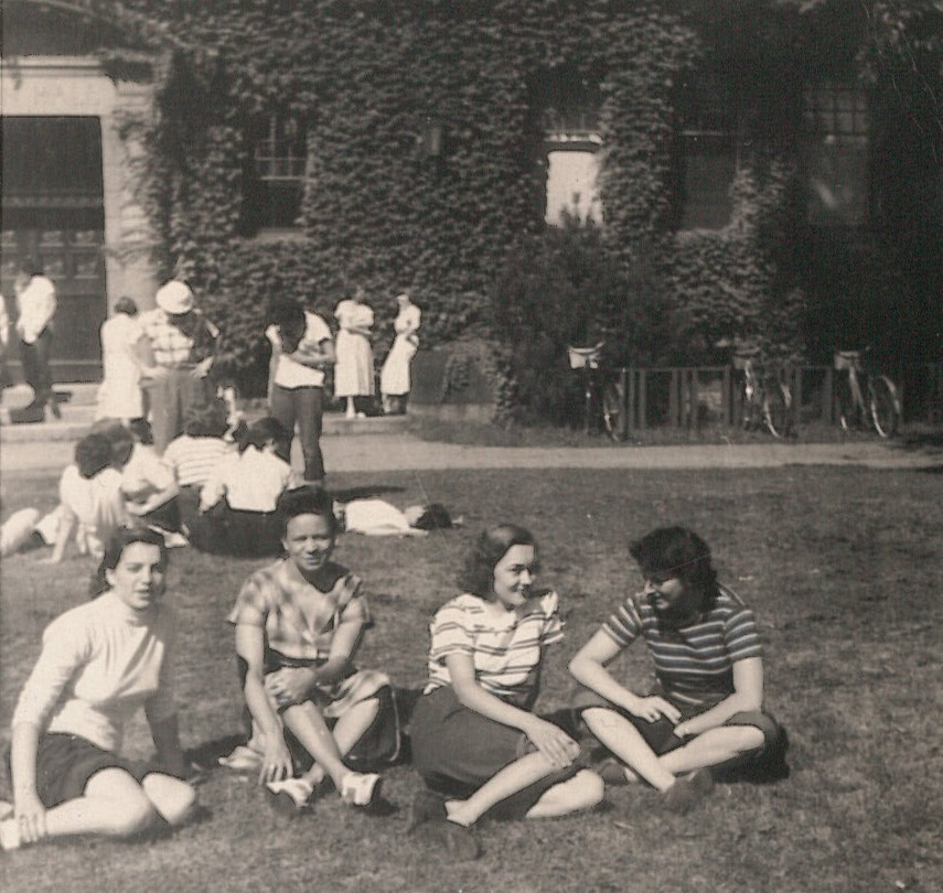 Black and white photo of several groups gathered on the lawn. In the foreground is an interracial group looking at the camera.