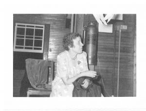 Black and white photo of Annette Garrette at an indoor party.