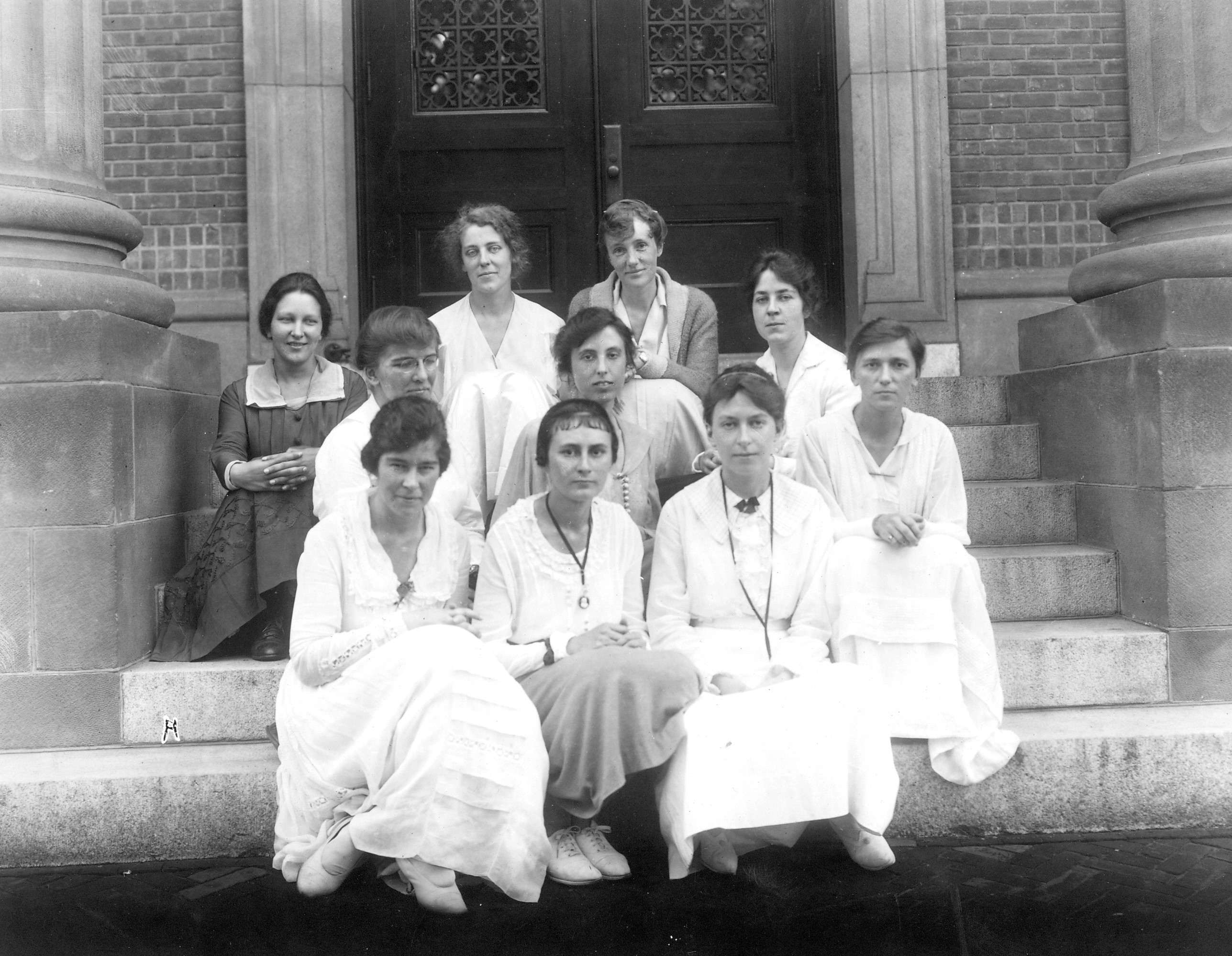 Black and white photo of ten women from the Smith School for Social Work, sitting on steps.