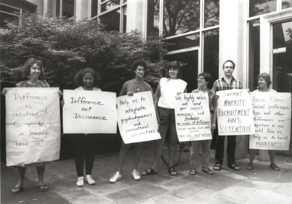 """Black and white photo of an interracial group of protesters. One sign says """"Difference not Dissonance"""""""