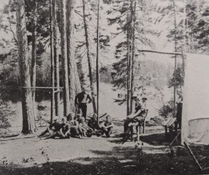 A group of campers and staffman standing on a campsite.